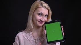 使用片剂和显示绿色屏幕的打手势赞许和微笑的成人白种人白肤金发的女性特写镜头射击  影视素材