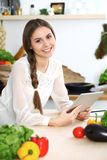 使用片剂的少妇,当烹调或做网上购物在厨房时 查寻照相机接近的表面的女孩 健康 库存图片