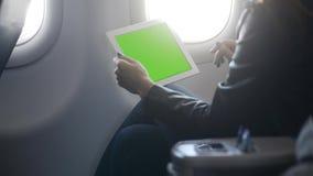 使用片剂的年轻女人在舒适飞机 股票录像