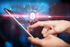 使用片剂的手有bitcoin链接网络和网上概念的 库存图片