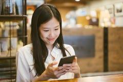 使用电话的年轻亚裔妇女在愉快的咖啡馆和微笑 库存照片