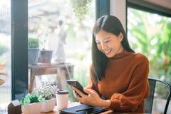 使用电话的年轻亚裔妇女在愉快的咖啡馆和微笑 库存图片
