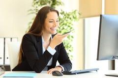 使用电话语音识别的愉快的办公室工作者 免版税库存图片