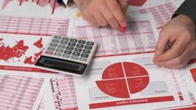 使用计算器的商人会计为计算在书桌办公室的财务 企业财务会计概念 红色报告 股票录像