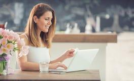 使用计算机和信用卡的有吸引力的年轻女人网络购物在家庭厨房里 图库摄影