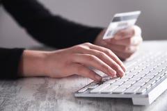 使用计算机和拿着信用卡的手 拟订dof重点现有量在线浅购物非常 免版税库存图片