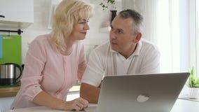 使用计算机的愉快的年长家庭在公寓厨房 股票视频