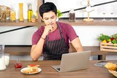 使用膝上型计算机的亚裔年轻人为联机工作 免版税库存照片