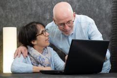 使用膝上型计算机的愉快的资深夫妇在家 免版税库存照片