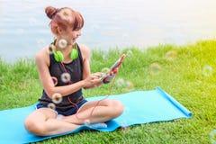 使用耳机听的音乐的美丽的亚裔妇女与智能手机或片剂在草在室外公园 户外绿色横向本质 免版税库存图片