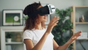 使用虚拟现实玻璃的愉快的非裔美国人的女孩画象移动手和微笑然后休假耳机 股票录像