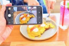 使用采取的智能手机的手食物摄影 库存照片