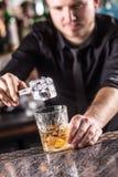 使酒精鸡尾酒饮料的专业男服务员古板 库存图片