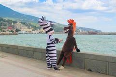 作为马和斑马打扮的设计卡通者在海边旅游城市的江边 免版税图库摄影