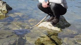 低角度观点的海岩石的人与鱼网在水中 股票视频