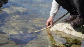 低角度观点的海岩石的人与鱼网在水中 股票录像