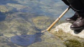 低角度观点的海岩石的人与鱼网在水中 影视素材