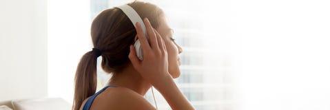 侧视图女性佩带的耳机在家享受喜爱的音乐 免版税库存照片