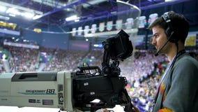 侧视图照相机操作员影片在体育场的曲棍球赛 股票录像