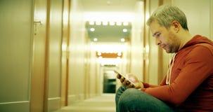 便服的帅哥在旅馆走廊使用他的智能手机 股票视频