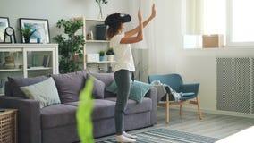 便衣的苗条少女在轻的屋子和移动的手里使用在家站立被增添的现实的玻璃 影视素材