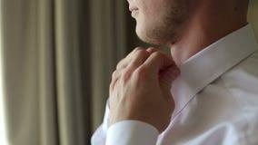供以人员他的站立在一个明亮的窗口的前面的白色衬衣的按钮 影视素材