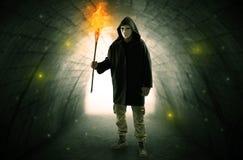 供以人员走与在一个黑暗的隧道的灼烧的大烛台 库存图片
