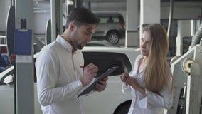 俏丽的女性经理告诉英俊的客户如何填好机器修理合同和微笑在汽车服务 股票视频