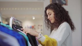 俏丽的妇女在服装店的运动衫看,采取挂衣架 影视素材