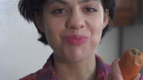 俏丽的少女特写镜头画象首先咬住和嚼一个大黄瓜的,然后在的一棵新鲜的红萝卜 股票视频