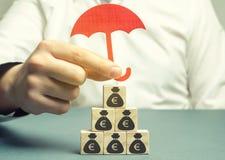 保险代理公司保护与欧元的图象的木块 储款保护 保持金钱安全 投资和资本 免版税库存照片