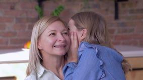 信任母亲,小愉快的女儿在家告诉心爱的在耳朵的妈妈耳语的秘密