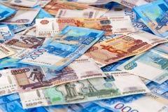俄国现金金钱5000,2000年,1000,说谎在飞机上的500 卢布作为背景,特写镜头的钞票 图库摄影