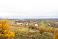 俄国风景在秋天 平原的看法与河的 鲁卡维什尼科夫庄园在Podviazye村庄  免版税库存照片