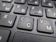 俄语-英语膝上型计算机键盘的片段,与浅景深的一个图象 免版税图库摄影