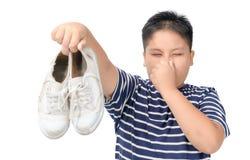 ?cklad fet pojke som rymmer ett par av stinkande skor arkivbilder