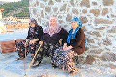 Ägäischer Bereich - alte Dorfbewohnerfrauen, die an der Windmühle sitzen Lizenzfreie Stockfotos