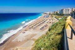 Ägäischer Strand mit Sonnenschutz in der Stadt von Rhodes Rhodes, Griechenland Stockbilder