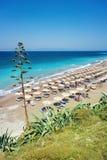 Ägäischer Strand mit Sonnenschutz in der Stadt von Rhodes Rhodes, Griechenland Lizenzfreie Stockfotografie