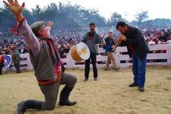 Ägäischer Volkstänzermann, der Tanz durch ein Knie aus den Grund mit einem Schlagzeuger und einer Fanfare durchführt stockfoto