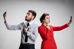 äganderätt för home tangent för affärsidé som guld- ner skyen till De två unga kollegorna som rymmer mobiltelefoner på grå bakgru Royaltyfria Foton