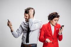 äganderätt för home tangent för affärsidé som guld- ner skyen till De två unga kollegorna som rymmer mobiltelefoner på grå bakgru Arkivbilder