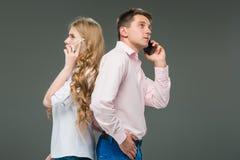 äganderätt för home tangent för affärsidé som guld- ner skyen till De två unga kollegorna som rymmer mobiltelefoner på grå bakgru Arkivfoto