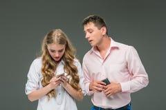 äganderätt för home tangent för affärsidé som guld- ner skyen till De två unga kollegorna som rymmer mobiltelefoner på grå bakgru Royaltyfri Foto