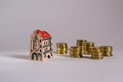 äganderätt för home tangent för affärsidé som guld- ner skyen till Modell av hushotellet med mynt Royaltyfri Fotografi