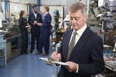 Ägare av teknikfabriken med personalen i bakgrund royaltyfria bilder