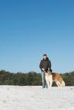 Ägare med räddningsaktionhunden i snö royaltyfri foto