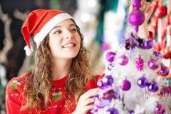 Ägare som ler, medan dekorera julgranen på Arkivbilder