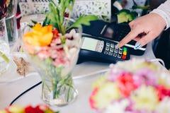 Ägaren av blomsterhandlaren shoppar skriva in beloppet som ska betalas Royaltyfria Foton