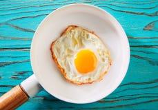 Ägg över lätt på den vita pannan Royaltyfri Bild